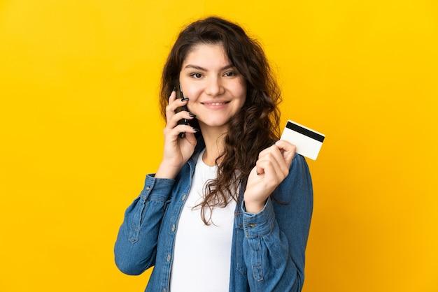Русская девушка-подросток изолирована на желтой стене, разговаривает по мобильному телефону и держит кредитную карту