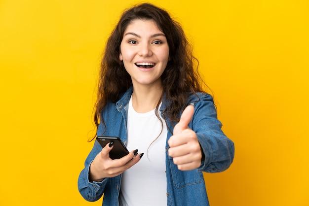 엄지 손가락을하는 동안 휴대 전화를 사용하는 노란색 벽에 고립 된 십 대 러시아 소녀