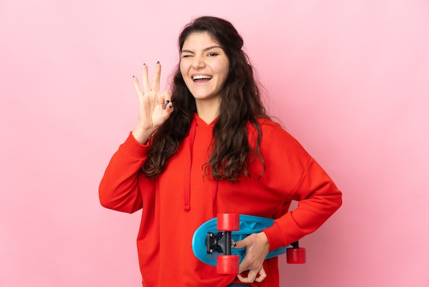 Teenager russian girl isolated on pink background with a skate and doing ok sign