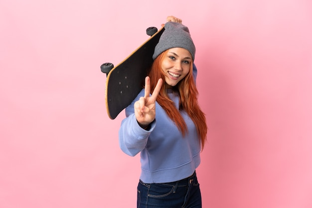 Teenager russian girl isolated on pink background with a skate doing victory gesture