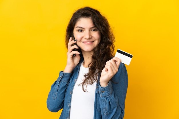 Teenager russian girl isolated on yellow wall keeping a conversation with the mobile phone and holding a credit card