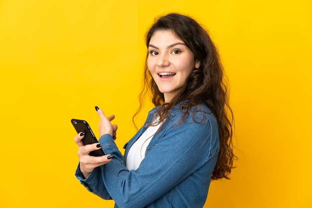 Teenager russian girl isolated on yellow wall using mobile phone and pointing back