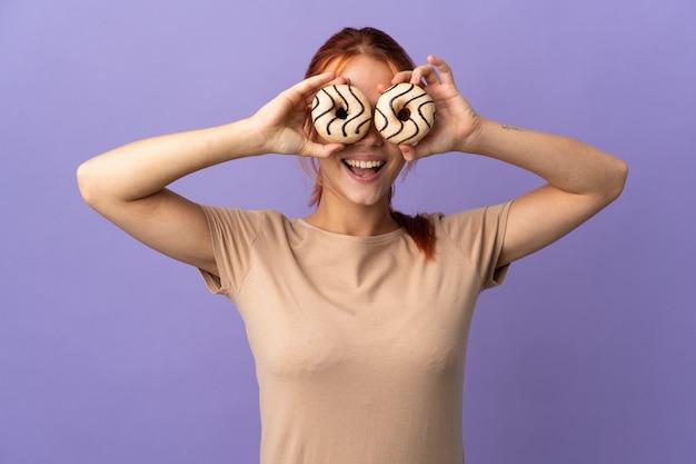 目の中にドーナツを保持している紫色の10代のロシアの女の子