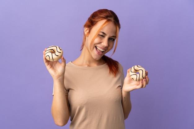 幸せな表情でドーナツを保持している紫色の10代のロシアの女の子