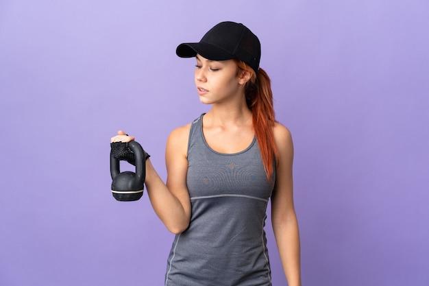 ケトルベルで重量挙げを作る紫色のティーンエイジャーのロシアの女の子