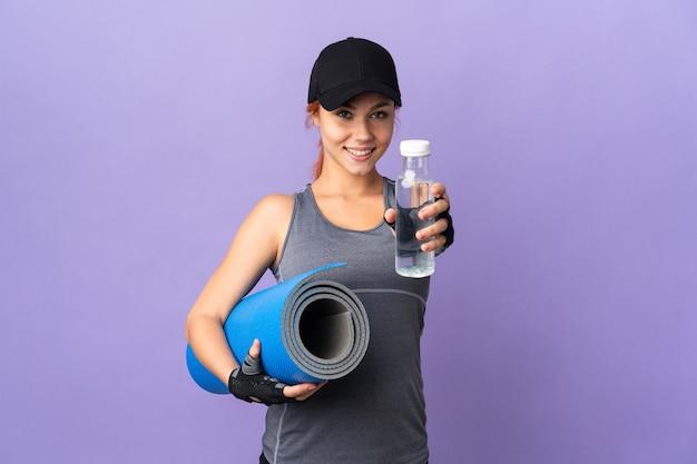 Русская девушка-подросток на фиолетовом со спортивной бутылкой с водой и с циновкой