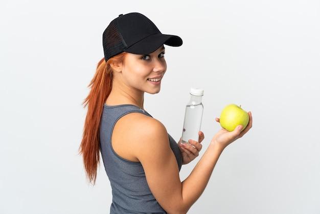 リンゴと水のボトルと白のティーンエイジャーのロシアの女の子