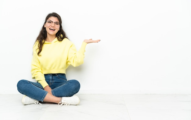 Русская девушка-подросток сидит на полу и держит на ладони воображаемое пространство, чтобы вставить рекламу