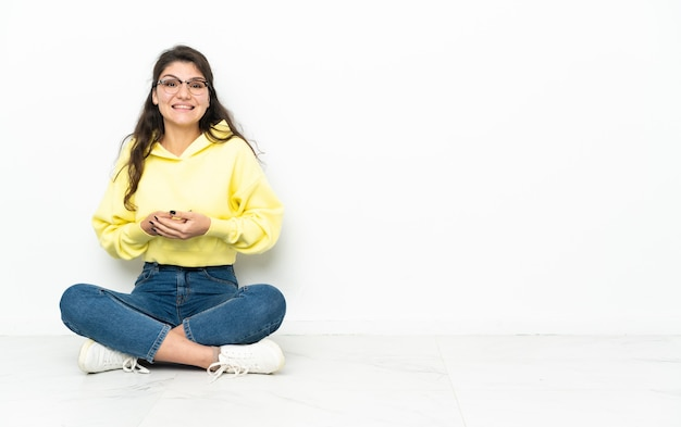 笑って床に座っている10代のロシアの女の子