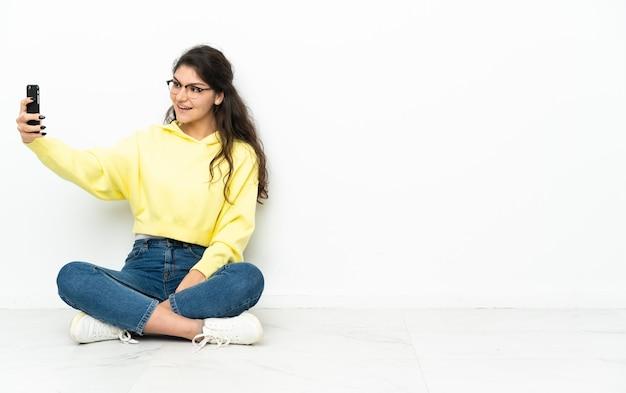 Русская девушка подросток сидит на полу, делая селфи
