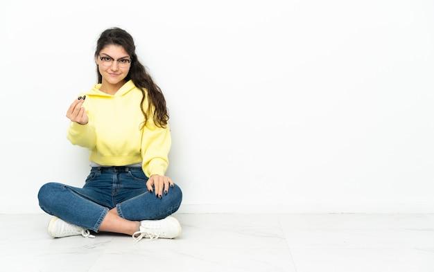 돈 제스처를 만드는 바닥에 앉아 십 대 러시아 소녀