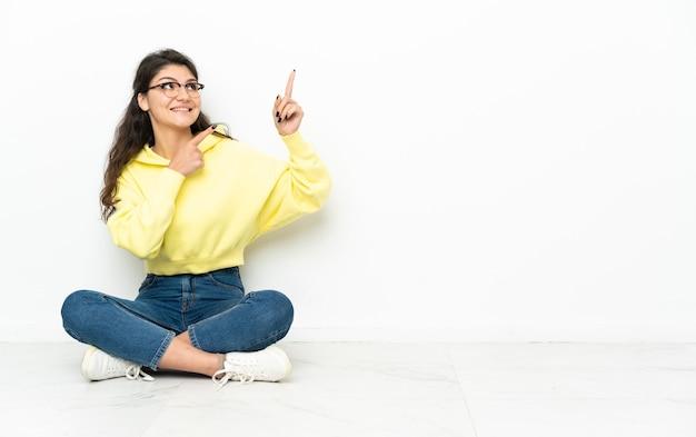 人差し指で指して床に座っている10代のロシアの女の子は素晴らしいアイデア