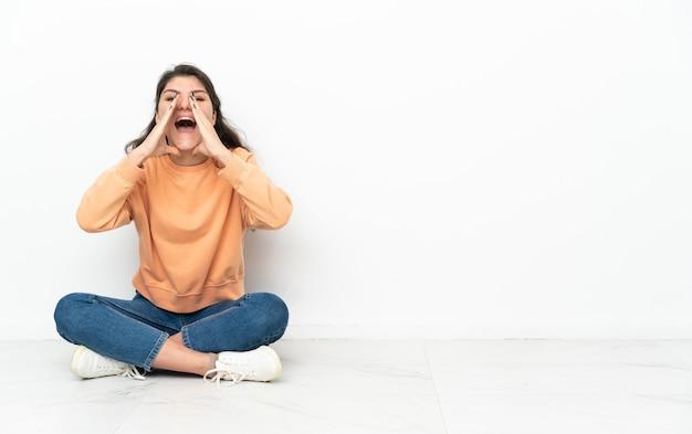 Русская девушка-подросток сидит на полу, кричит и что-то объявляет