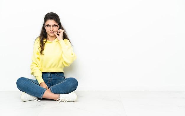 沈黙のジェスチャーの兆候を示す床に座っている10代のロシアの女の子