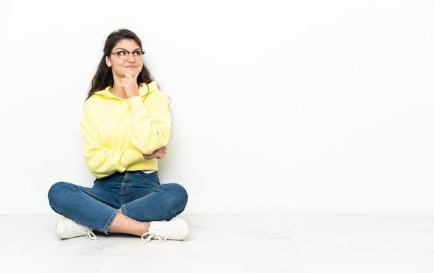 Русская девушка подросток сидит на полу, думая об идее, глядя вверх