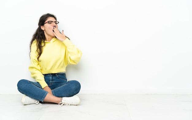 Русская девушка-подросток сидит на полу, зевая и прикрывая широко открытый рот рукой