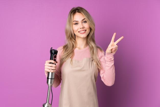 Русская девушка-подросток, использующая ручной блендер, изолирована на фиолетовой стене, показывая знак победы обеими руками