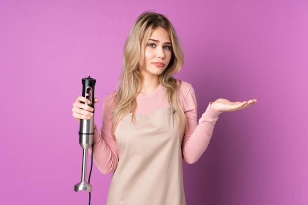 Русская девушка-подросток, использующая ручной блендер, изолирована на фиолетовой стене, недовольна тем, что чего-то не понимает
