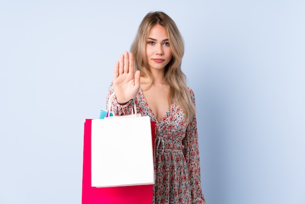 Teenager russian girl with shopping bag isolated on blue