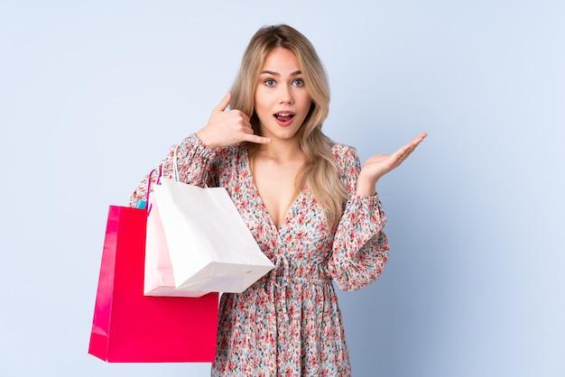 Русская девушка-подросток с сумкой для покупок изолирована на синем, делая телефонный жест и сомневаясь