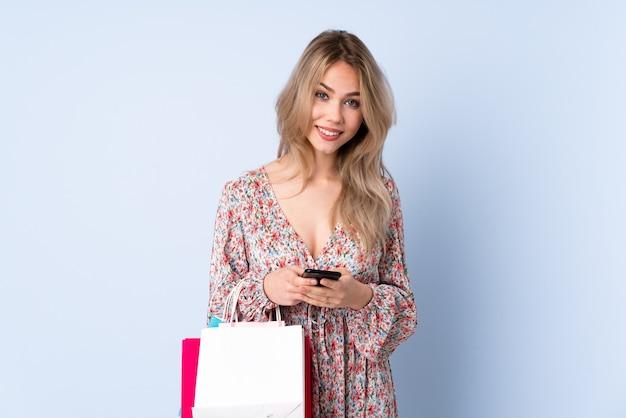 Русская девушка-подросток с хозяйственной сумкой, изолированной на синем, отправляет сообщение с мобильного телефона
