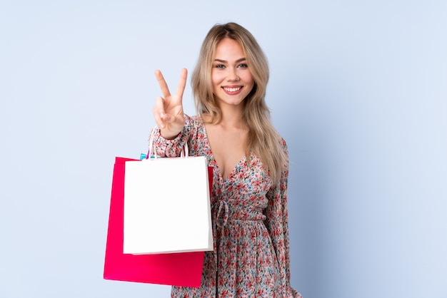 Русская девушка-подросток с хозяйственной сумкой, изолированной на синей стене, улыбается и показывает знак победы