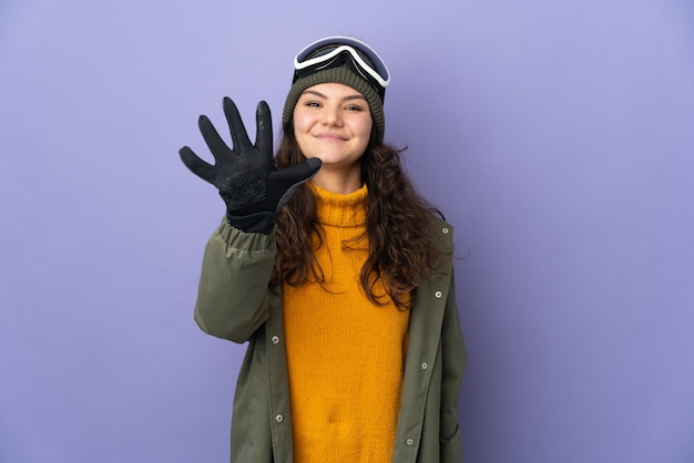 Русская девушка-подросток в очках для сноубординга, изолированные на фиолетовом фоне, считая пять пальцами