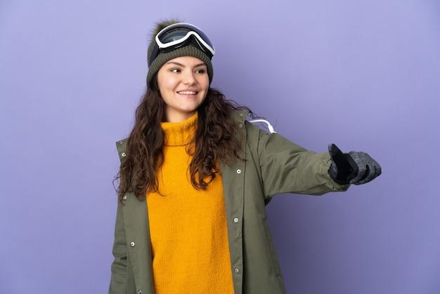 親指を立てるジェスチャーを与える紫色の背景に分離されたスノーボードグラスを持つ10代のロシアの女の子