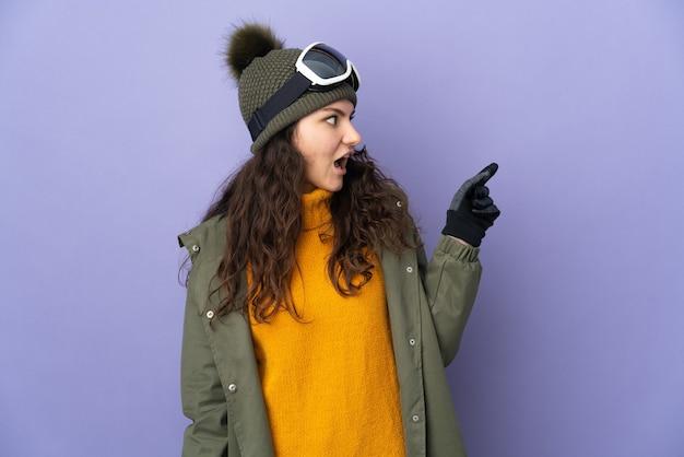 指を持ち上げながら解決策を実現することを意図して紫色の背景に分離されたスノーボードグラスを持つ10代のロシアの女の子