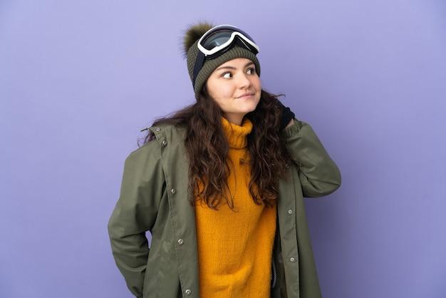 耳に手を置くことによって何かを聞いて紫色の背景に分離されたスノーボードグラスを持つ10代のロシアの女の子