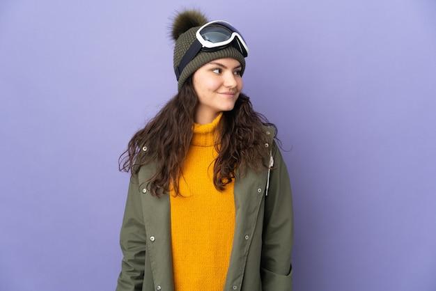 Русская девушка-подросток в очках для сноуборда, изолированные на фиолетовом фоне, глядя в сторону