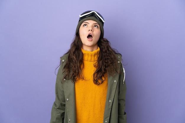 見上げると驚いた表情で紫色の背景に分離されたスノーボードグラスを持つ10代のロシアの女の子