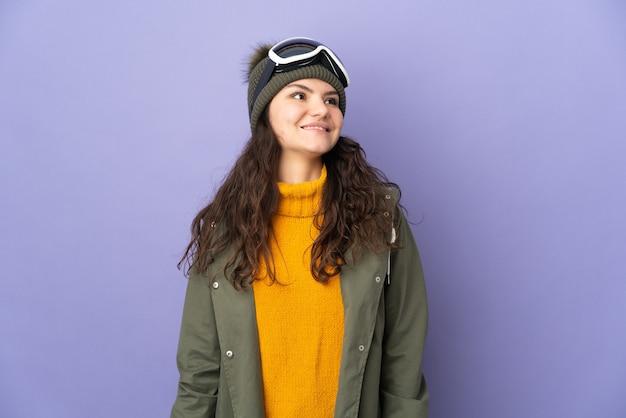 見上げながらアイデアを考えて紫色の背景に分離されたスノーボードグラスを持つ10代のロシアの女の子