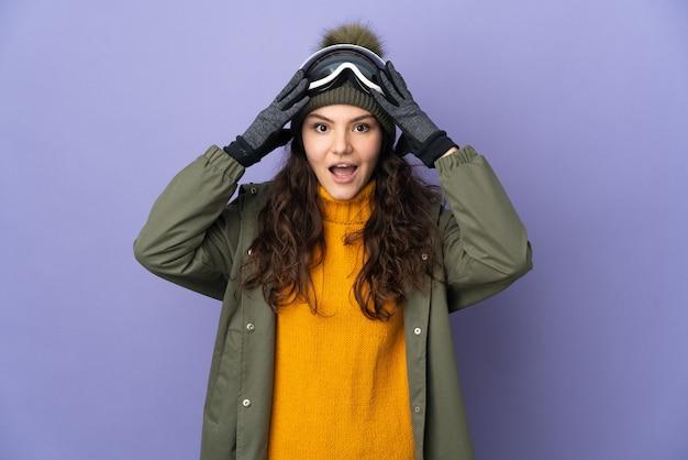 Русская девушка-подросток в очках для сноуборда изолирована на фиолетовом фоне с удивленным выражением лица