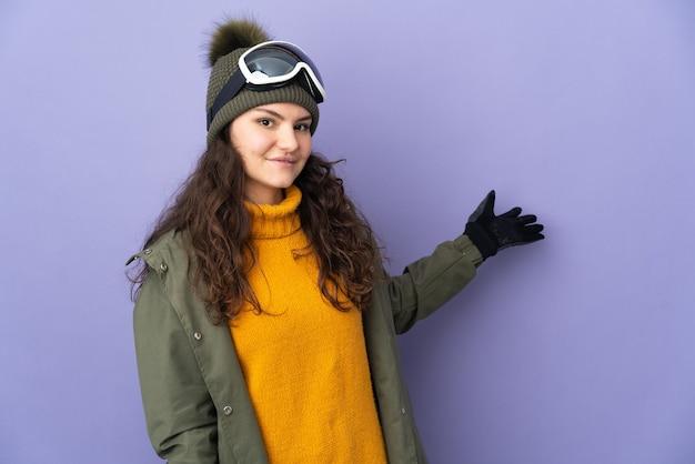 Русская девушка-подросток в очках для сноубординга изолирована на фиолетовой стене, протягивая руки в сторону, приглашая приехать