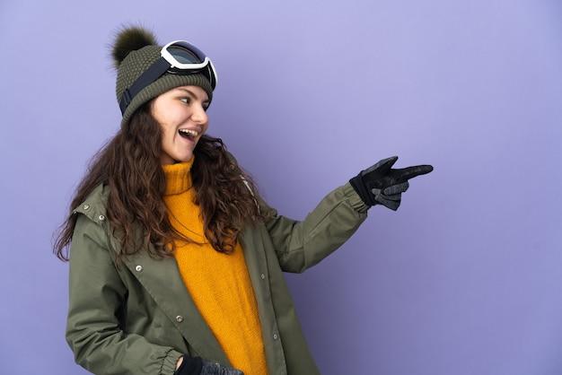 横に指を指し、製品を提示する紫色の壁に分離されたスノーボードグラスを持つ10代のロシアの女の子