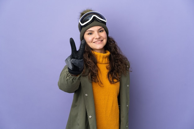 笑顔と勝利のサインを示す紫色の壁に分離されたスノーボードグラスを持つ10代のロシアの女の子