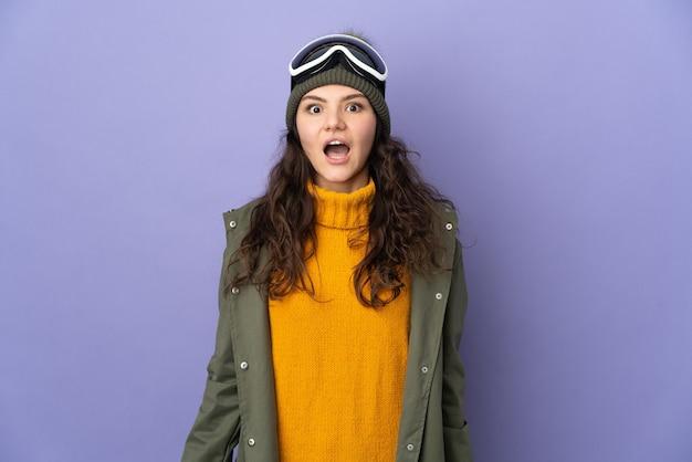 Русская девушка-подросток в очках для сноуборда изолирована на фиолетовой стене с удивленным выражением лица