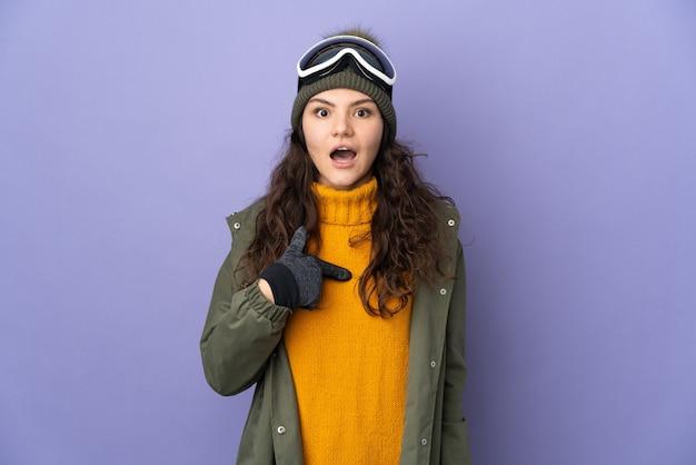 놀라운 표정으로 보라색 벽에 고립 된 스노우 보드 안경 십 대 러시아 소녀