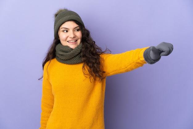 親指を立てるジェスチャーを与える紫色の背景に分離された冬の帽子を持つ10代のロシアの女の子