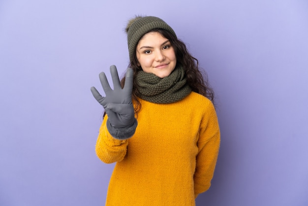 Русская девушка-подросток в зимней шапке изолирована на фиолетовом фоне счастлива и считает четыре пальцами