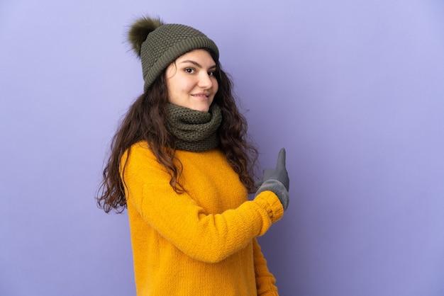 다시 가리키는 보라색 배경에 고립 된 겨울 모자와 십 대 러시아 소녀