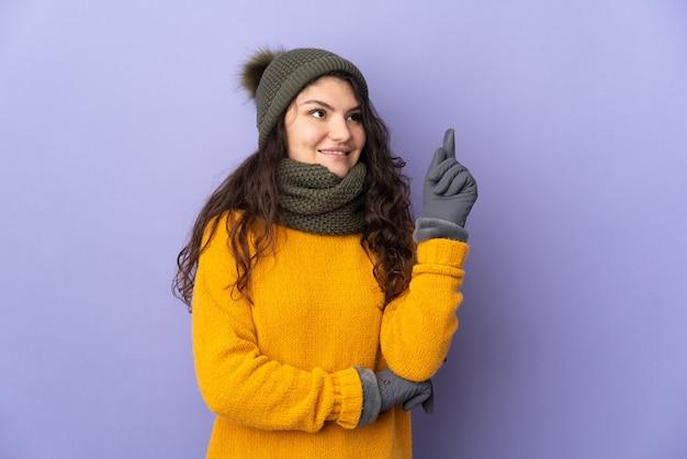 Русская девушка-подросток в зимней шапке изолирована на фиолетовом фоне, указывая на отличную идею