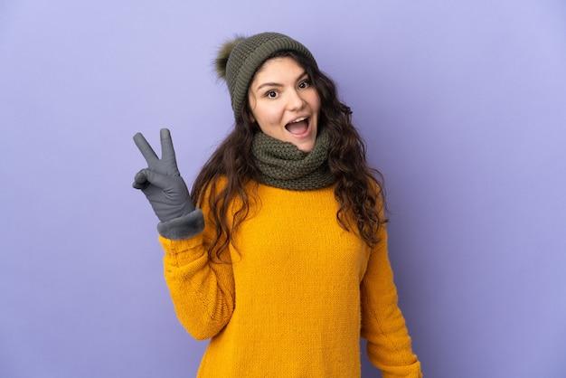 Русская девушка-подросток в зимней шапке, изолированные на фиолетовом фоне, улыбается и показывает знак победы