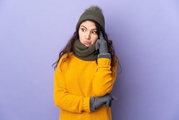 아이디어를 생각하는 보라색 배경에 고립 된 겨울 모자와 십 대 러시아 소녀