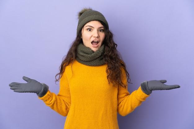 Русская девушка-подросток в зимней шапке изолирована на фиолетовом фоне с шокированным выражением лица