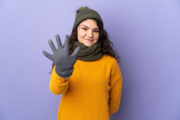 손가락으로 5 세 보라색 벽에 고립 된 겨울 모자와 십 대 러시아 소녀