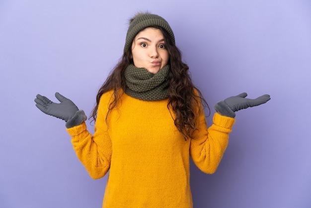 Русская девушка-подросток в зимней шапке изолирована на фиолетовой стене, сомневаясь, поднимая руки