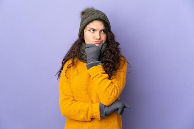 의심을 갖는 보라색 벽에 고립 된 겨울 모자와 십 대 러시아 소녀