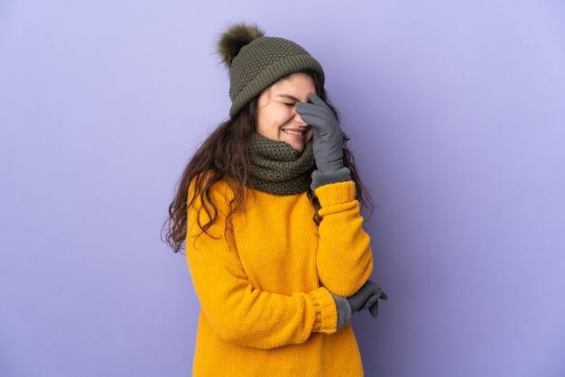 笑って紫色の壁に分離された冬の帽子を持つ10代のロシアの女の子